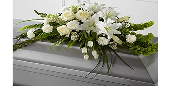 Casket with white flower arrangement on top